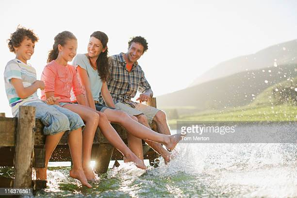 Family on dock splashing feet in lake