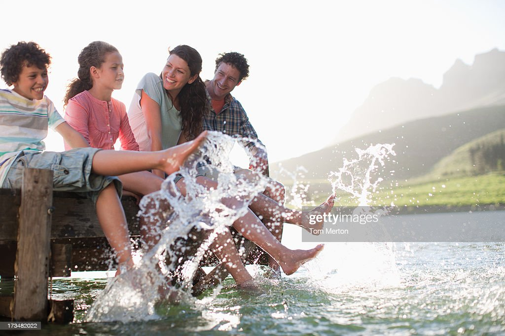 Family on dock splashing feet in lake : Stock Photo