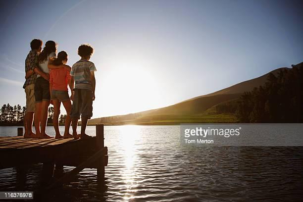 Famille sur dock en regardant le soleil se coucher sur le lac