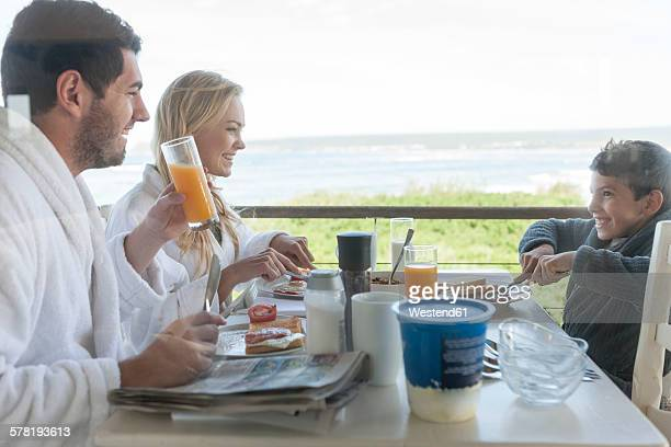 Family on patio of beach house eating breakfast