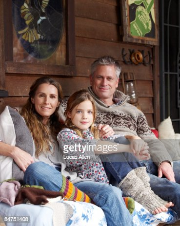 Family on porch outside country home : Stock Photo