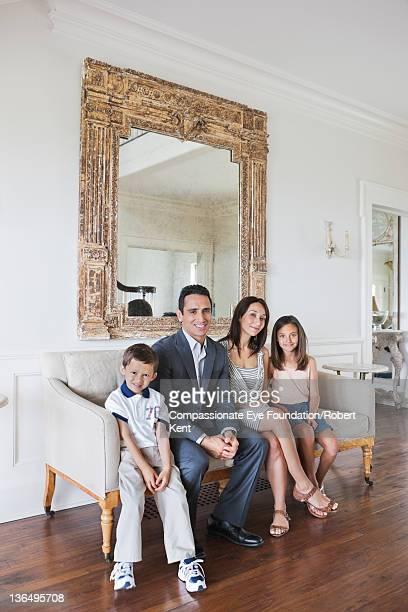 Family on sofa in living room, smiling