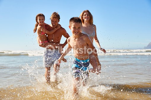 Family On Summer Beach Vacation Run Out Of Sea Towards Camera : Stock Photo