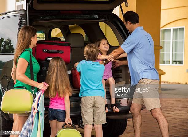 Famille en vacances d'été arrive à l'hôtel.   Bagages, l'entrée du complexe.