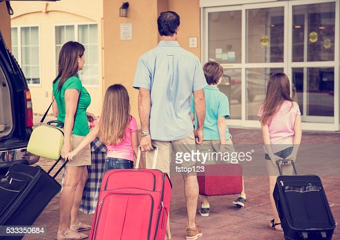 Family on summer vacation arrives at hotel. Luggage, resort entrance.