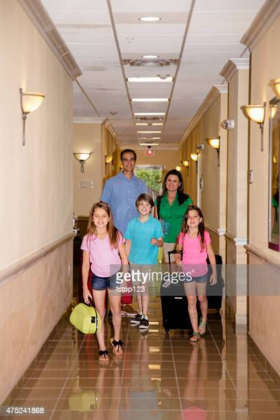 Family on summer vacation walking down hotel hallway. Excited.