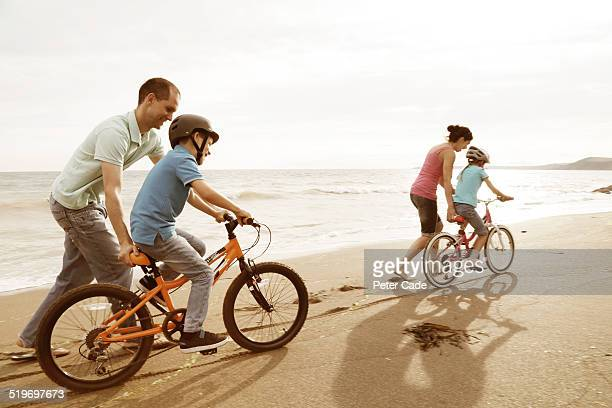 Family on the beach helping kids to ride bikes .