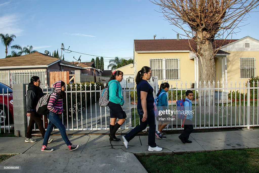 A family on their way to school walks by the residence where a year-old girl died in a shooting on 300 N. Holly Avenue on February 10, 2016 in Compton, California. Authorities are searching for two men believed responsible for the shooting death during a suspected gang attack on February 9.