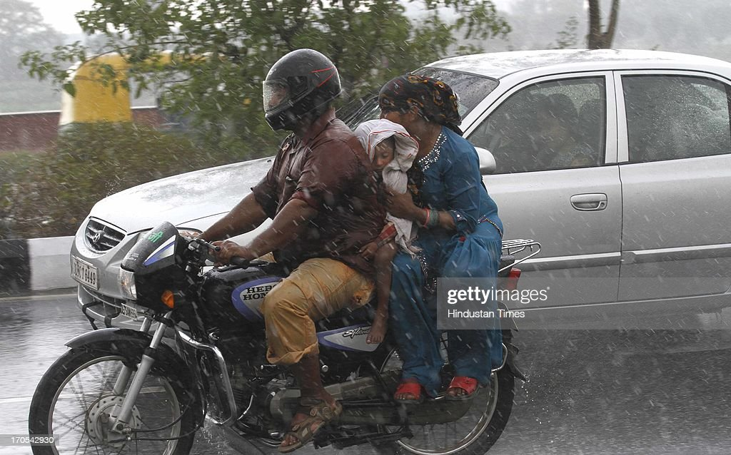 A family on two-wheeler get drenched during the heavy pre monsoon rain on June 14, 2013 in New Delhi, India. The city received 11.6 mm rainfall and the humidity oscillated between 47 and 91 percent.
