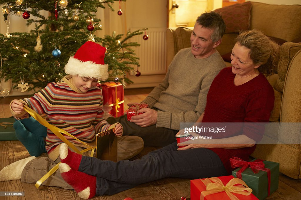 Family opening presents at christmas. : Foto de stock