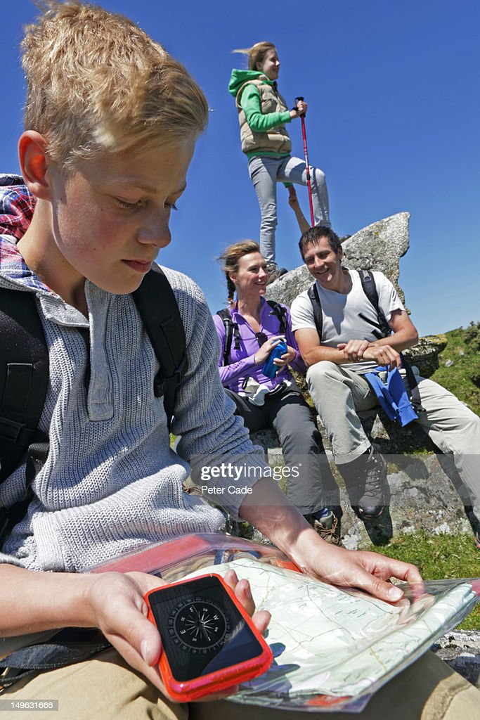 family out walking, boy checking map : Stock Photo