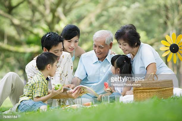 Family outdoors at park having picnic and looking at book