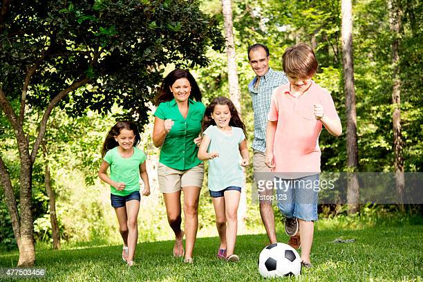 Family outdoors in summer playing soccer game. Park.