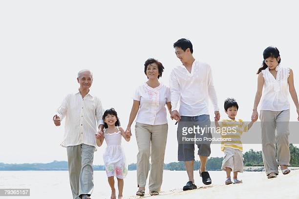 Family outdoors on beach holding hands