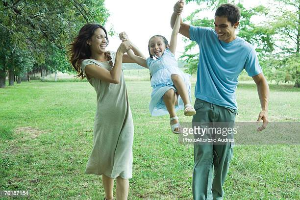 'Family outdoors, parents swinging girl'