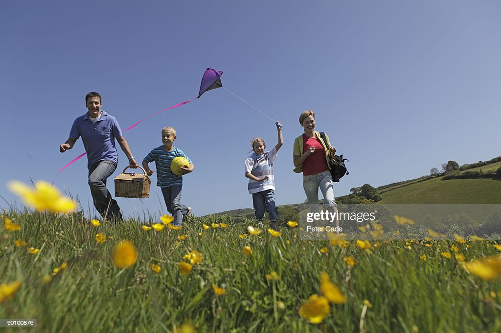 family outdoors together flying kite : Stock Photo