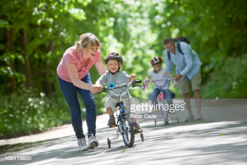 Family outside, children learning to ride bikes : Stock Photo