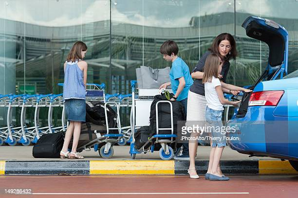 Family outside of airport unloading luggage from taxi trunk
