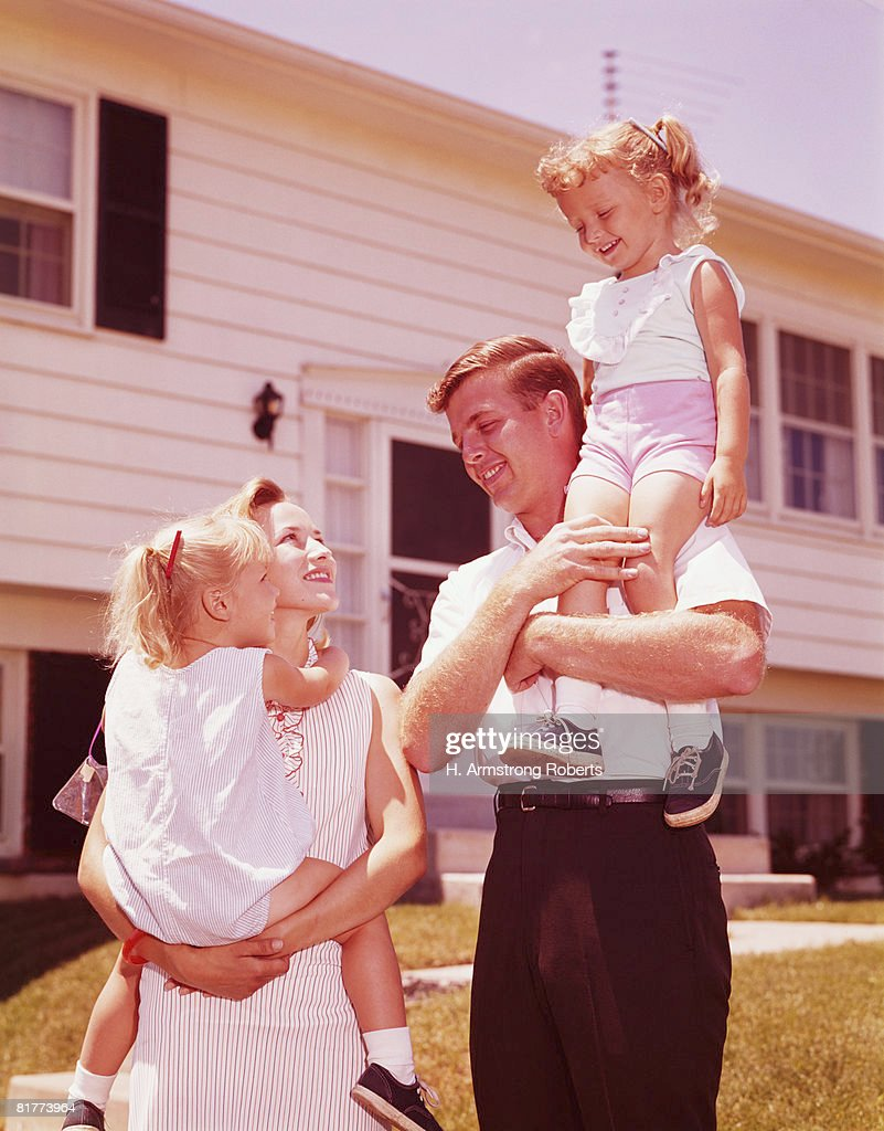 Family outside suburban home. (Photo by H. Armstrong Roberts/Retrofile/Getty Images) : Stock Photo