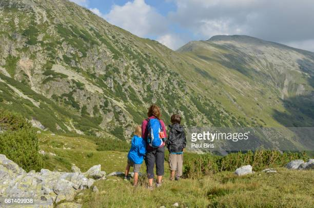 Family overlooking view from rural hillside, Retezat Mountains, Romania