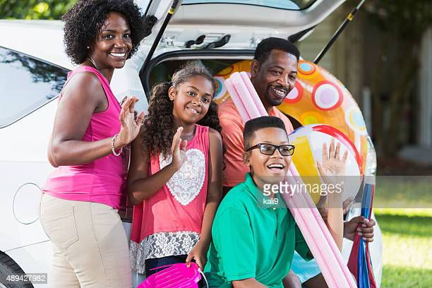 Family packing car for trip to the beach or pool