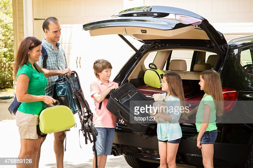 Family packing car to go on summer vacation. Parents, children.