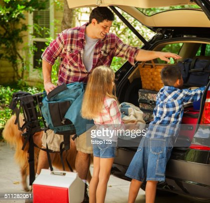 Family packing car to go on vacation. Father, children.