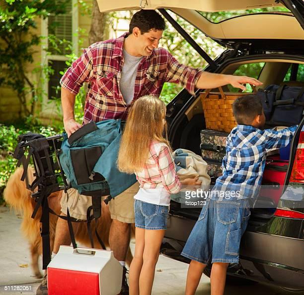 Famille emballage voiture pour partir en vacances.  Père et enfants.