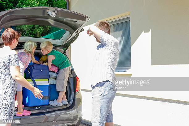 Family packing car to go on vacation.