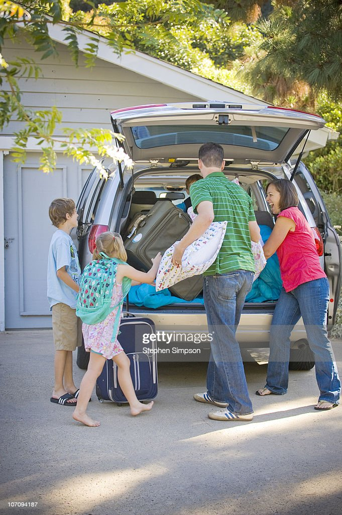 family packing for vacation in their driveway