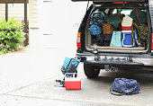 Family of four packs vehicle for a autumn hiking and camping trip.  Two parents and two children with SUV fully packed.