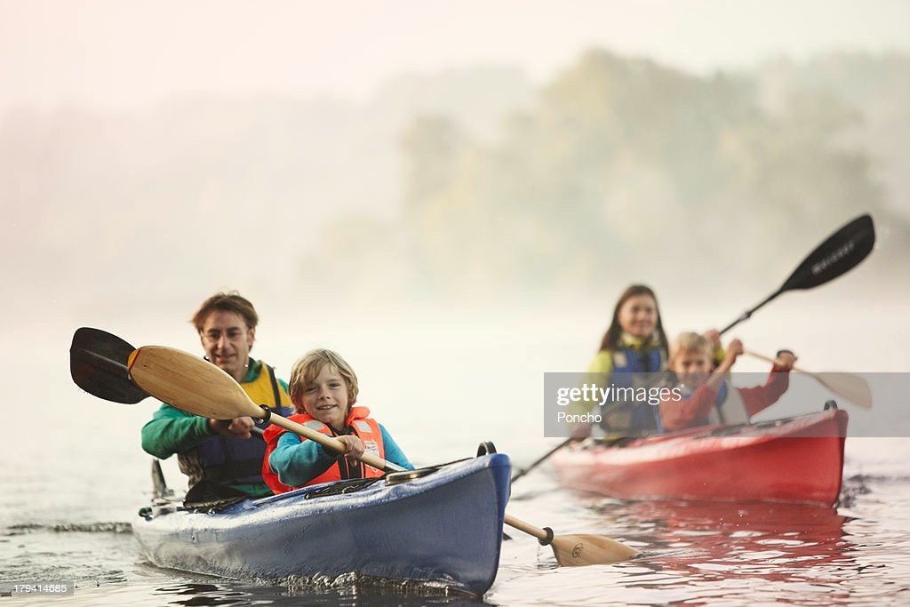 Family paddling in a canoe on a lake : Stock Photo