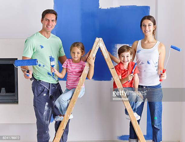 Family painting wall blue together
