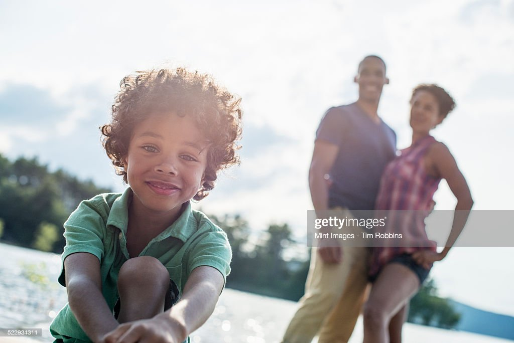 A family, parents and son spending time together by a lake in summer.
