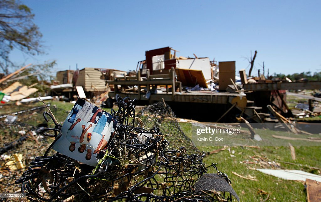 A family photo sits intertwined in a tangled fence amongst destroyed homes caused by tornadoes on April 29, 2011 in Pratt City, Alabama. Alabama, the hardest-hit of six states, is reported to have had nearly 300 deaths as a result of the storms.