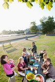 large get together / fam'ly at picnic table / picnic in the park.
