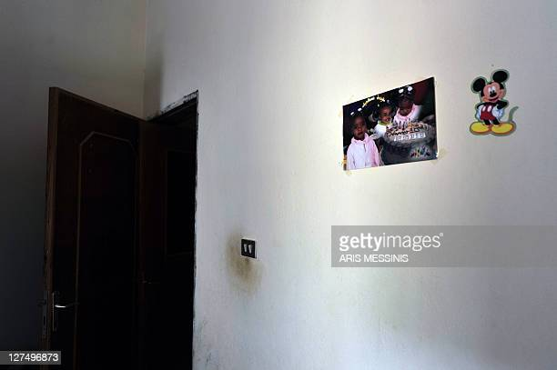 A family picture and a Mickey Mouse sticker decorate a wall at an abandoned house in the Libyan town of Tawarga on September 25 2011 The people of...