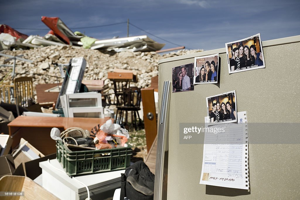 Family pictures are displayed among the rubble of a house belonging to Israeli settlers that was demolished by Israeli police in the outpost of Maale Rehavam, in the Israeli occupied Palestinian West Bank, on February 13, 2013. The house was built without any authorization outside the larger state-sanctioned settlement. The number of Israeli settlers in the occupied West Bank grew by 4.7% in 2012, according to figures obtained by AFP from a settler organisation. AFP PHOTO JANOS CHIALA