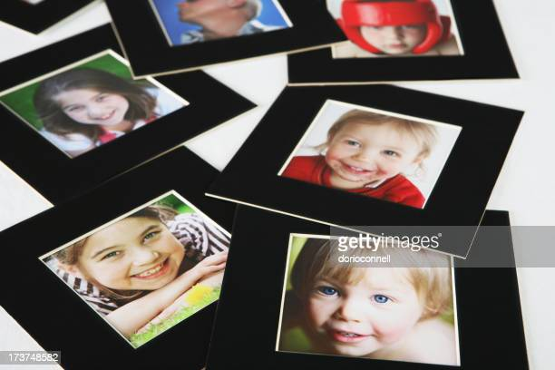 Family pictures in black frame scattered on white surface