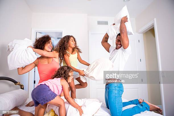 Family pillow fighting on bed, smiling