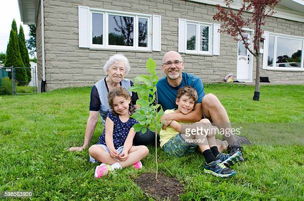 Family planting a tree on front yard