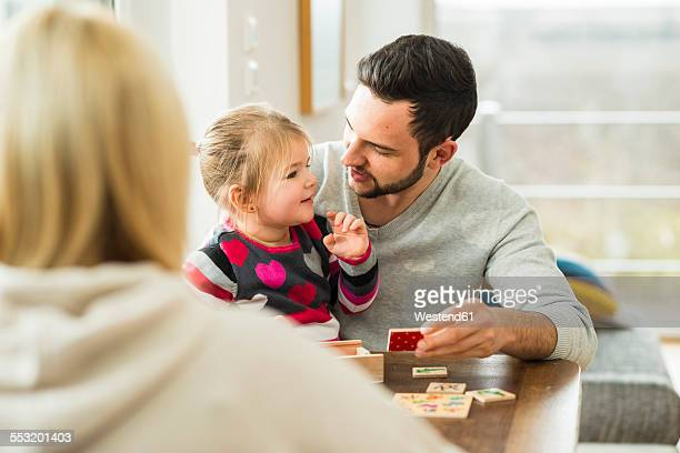 Family playing a game at wooden table