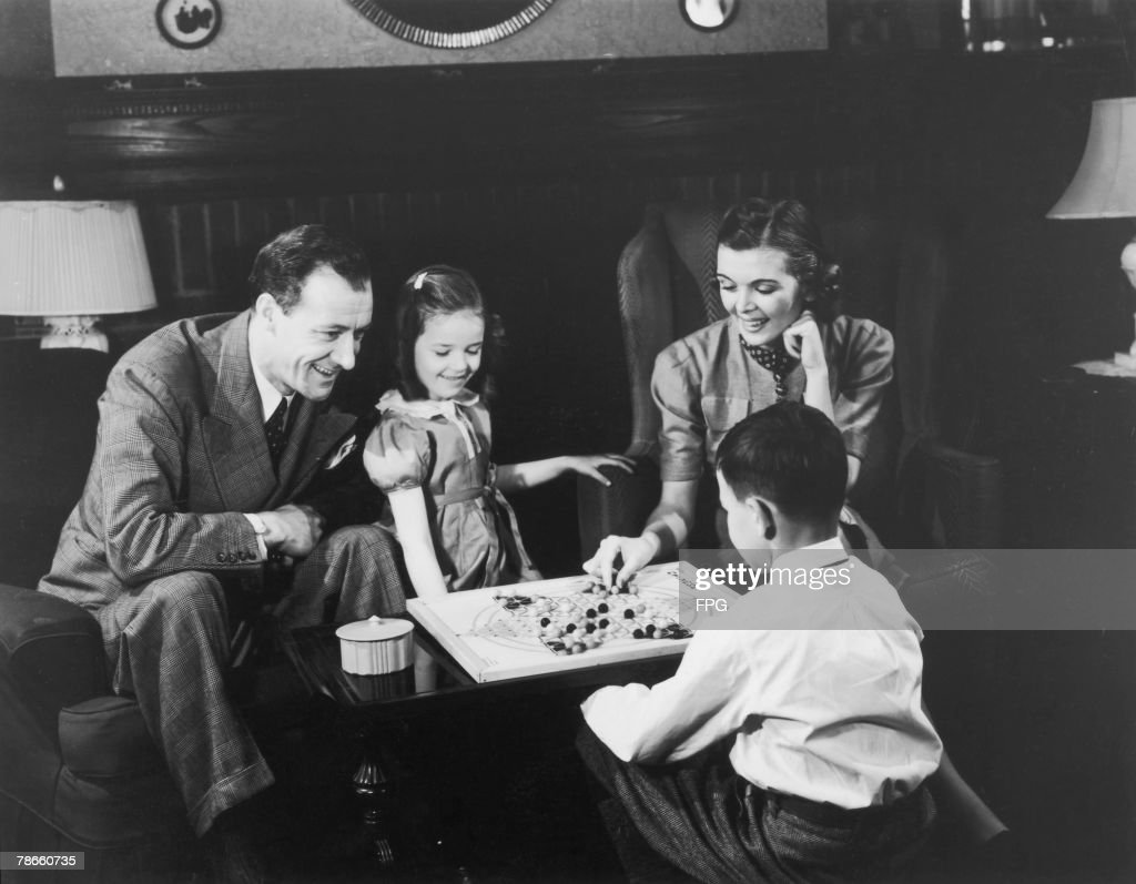 A family playing a game of chinese chequers together at home circa 1945