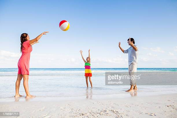 Family playing ball in the beach