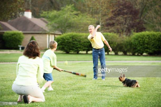 Family playing baseball in the garden
