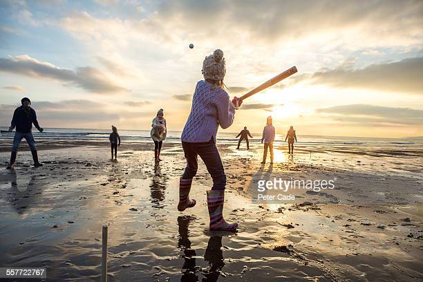 family playing baseball on beach at sunset.