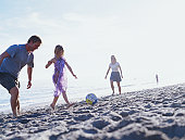 Family playing beach football.