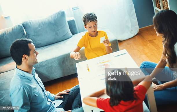 Family playing board game at home.