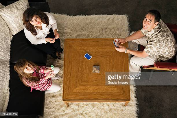 Family playing card game around coffee table