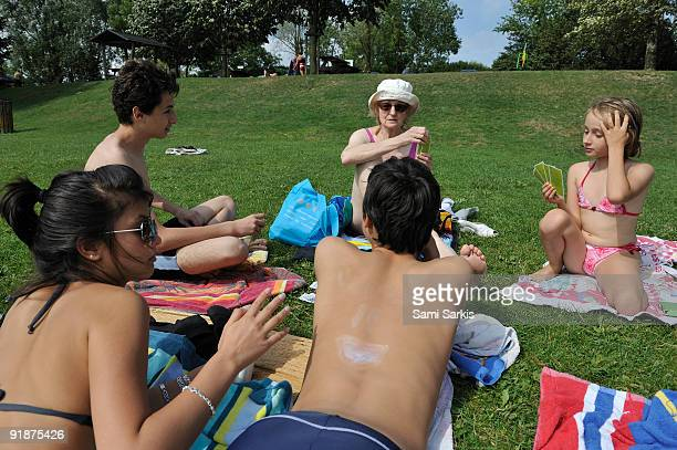 Family playing cards at beach, lying on grass